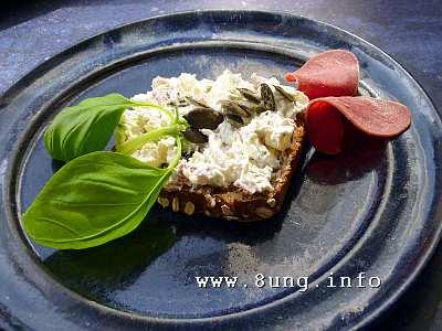 Brot mit Frischkäse-Zubereitung, Rinderzunge und Basilikum auf blauem Teller