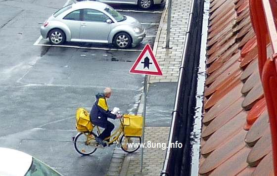 Postbote auf dem Fahrrad bei Regen