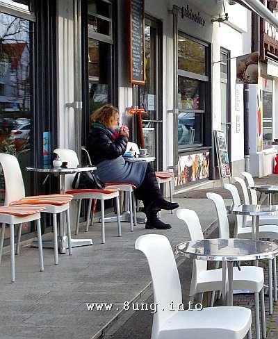 Raucherin in einem leeren Strassencafe - dick eingepackt
