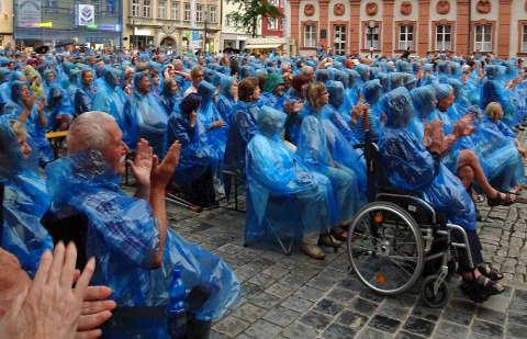 In blauen Regencapes klatschen die Zuschauer des Openair-Konzertes