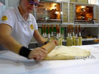 Bäckerin rollt Hefetig für Baumkuchen