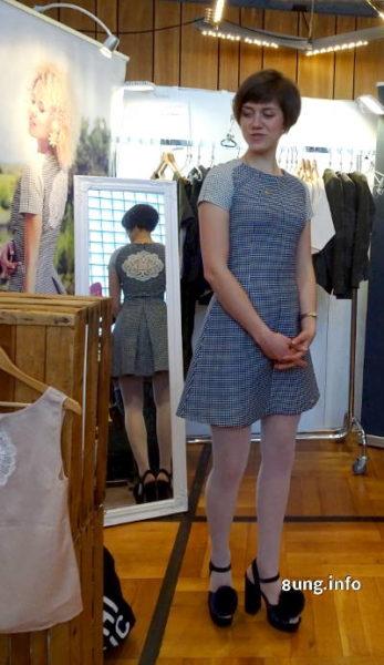 Designerin mit kurzem Kleid und Bommeln auf den Sandalen