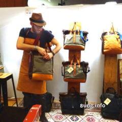 Designer mit Lederschürze, Hut, Taschen