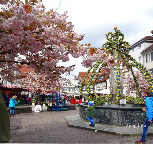 Rosa Blüten und gelb-grüner Osterbrunnen
