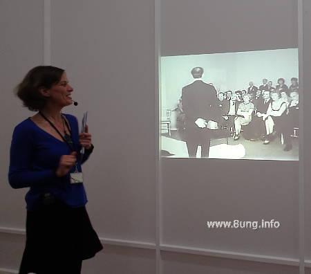 Yves Klein im Museum Bozar - Film von einer Performance. Yves Klein bei der Einführung im Vordergrund (mit Anzug und Krawatte), dahinter das Kunst-Publikum.