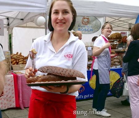 bäckereifachverkäuferin bietet Brot zum Probieren an