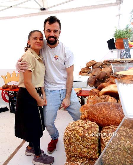 großer Bäcker und kleine Verkäuferin am Brotstand