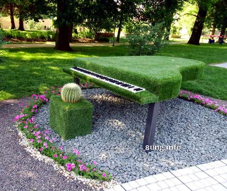 Klavier und Hocker mit Gras bewachsen