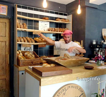 Bäcker sortiert sein Brot im Laden ins Regal
