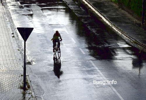 Radfahrer im Regen, die Sonne im Rücken