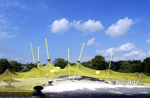 gelbes Sportnetz, blauer Himmel, Schönwetterwolken