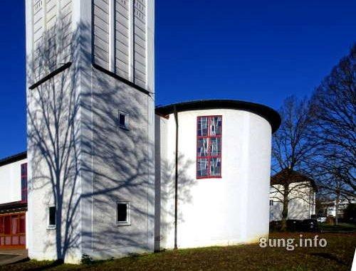 Baumschatten auf weißem Kirchturm vor blauem Winterhimmel