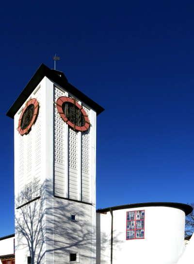 Weiße Kirche mit Baumschatten vor blauem Winter Himmel