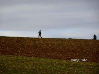 Spaziergänger vor grauem Himmel, dunkles Feld