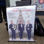 3 Tenöre mit einem Plakat, auf dem sie ihr Repertoire anzeigen