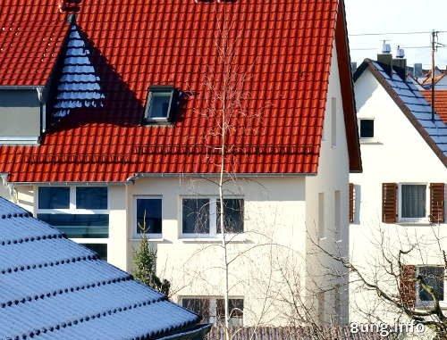 Schnee im Schatten auf roten Dächern