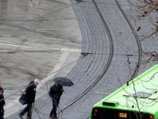 Passanten bei Regen und Wind auf dem Weg zur Strassenbahn