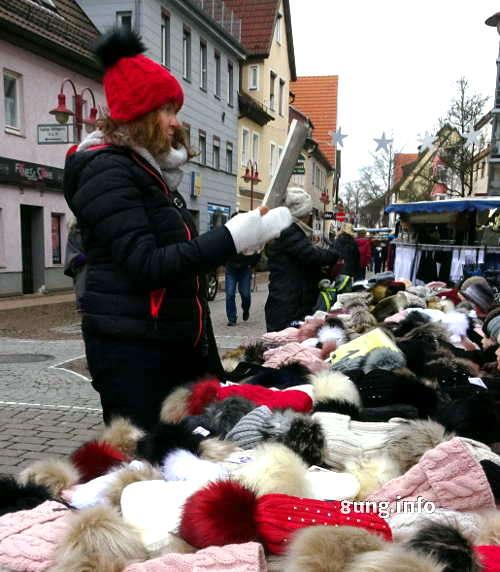 Kundin probiert rote Pudelmütze auf dem Krämermarkt