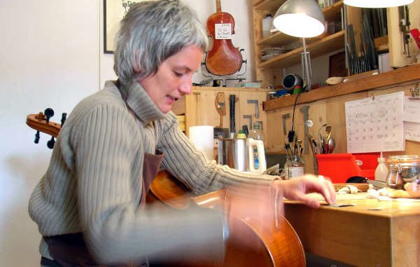 Geigenbaumeisterin bei der Arbeit an einem Cello