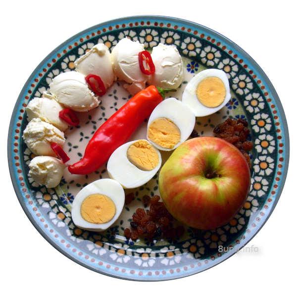 Paprika, Eier, Apfel, Rosinen auf einem bunten Keramikteller