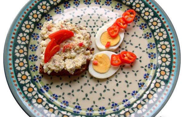 Paprika, Eier, Apfel auf einem bunten Keramikteller angerichtet