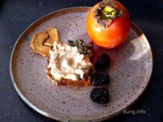 Khaki, Trockenobst, Kürbiskerne mit Frischkäse, angerichtet auf einem Keramikteller