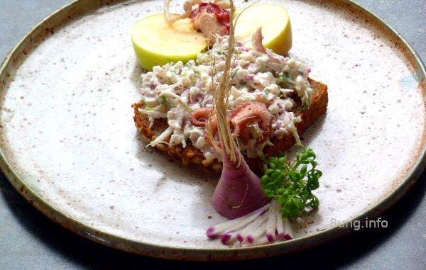 Meeresfrüchte, Rettich, Apfel, Kresse, Senfkörner auf dem Teller angerichtet