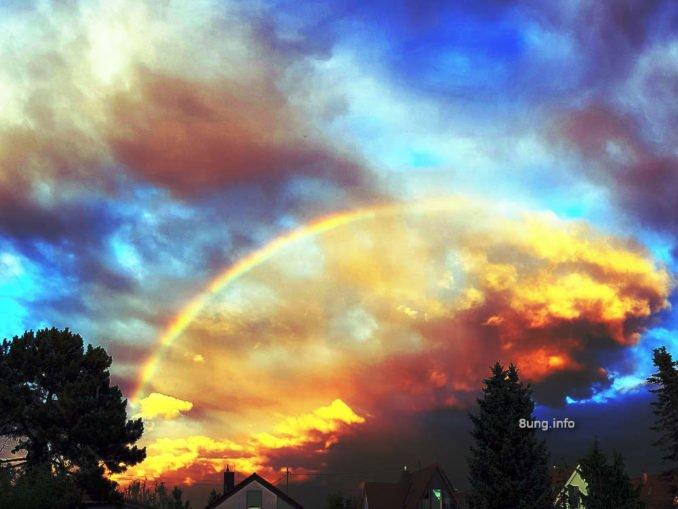 Feuriger Regenbogen vor blauem Himmel