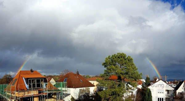 Regenbogen, von grauen Wolken verdeckt