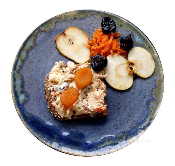 Apfelscheibe, Birnenscheibe, geraspelte Möhren, Backpflaumen und getrocknete Aprikosen mit Frischkäsecreme auf einer Scheibe Vollkornbrot
