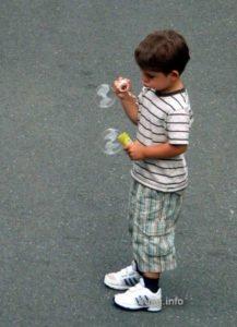 Kind mit Seifenblasen, ins Spiel vertieft