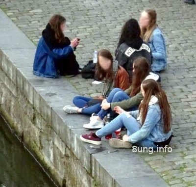 Mädchen sitzen auf den Pflastersteinen am Fluss