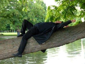 Mann liegt auf dem Ast