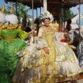 Dame in goldenem Rokokokleid auf einem Karussell