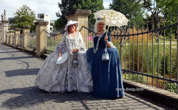 2 Damen in Barockkostümen vor einem Gitter