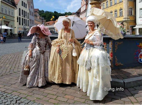 3 Damen in Barockkleidern auf dem Marktplatz