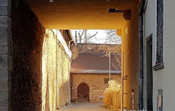 Blick durch den Torbogen in den sonnigen Hof