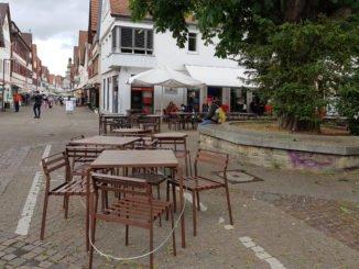 leere Tische und Stühle im Strassencafe, graue Wolken
