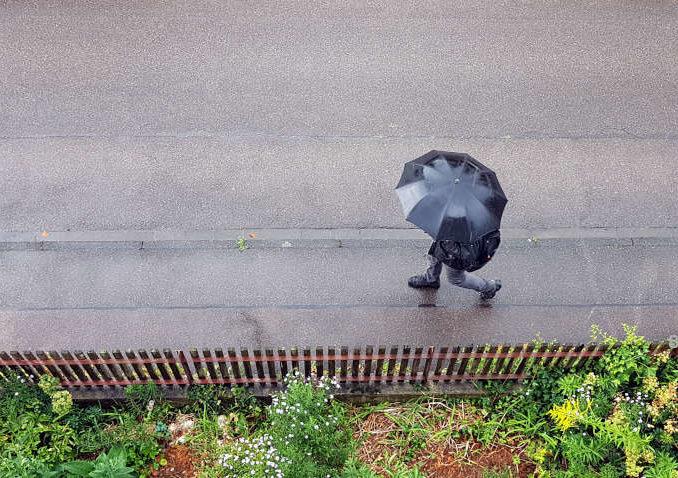Fussgänger mit schwarzem Regenschirm