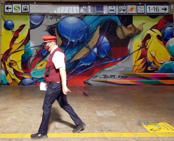Graffiti im Bahnhof Stuttgart - abstraktes Riesengemälde und Bahnmitarbeiter
