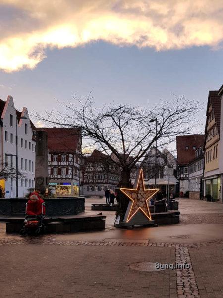 leerer Marktplatz, Weihnachtsstern, dunkle Wolken mit Sonne am Rand