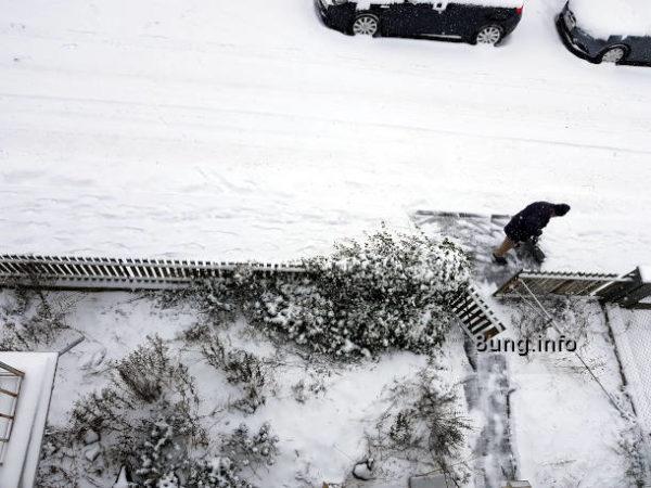 Wetter im Februar - Vorgarten im Schnee, Mann schippt Schnee