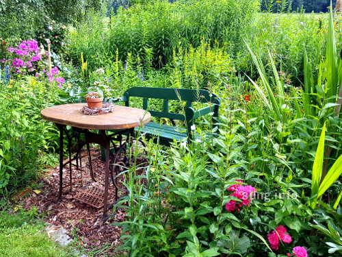 Garten im Sommer: Gartenbank mit Tisch - alte Nähmaschine