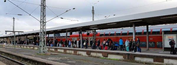 Reisende warten auf dem Gleis am Bahnhof
