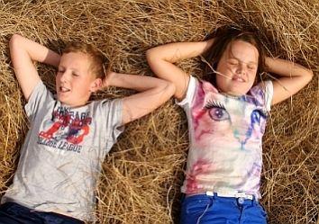 2 Bauernkinder bei einer Pause im Stroh