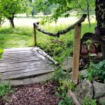 Holzsteg über den Bach, Baumringe mit Keramikeulen