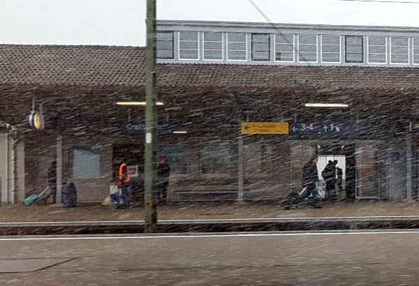 Schneegestöber auf dem Bahnhof, Reisende mit Koffern