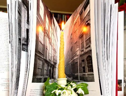 Schneeglöckchen im Kerzenhalter mit Fotobuch über Häuserschluchten im Hintergrund