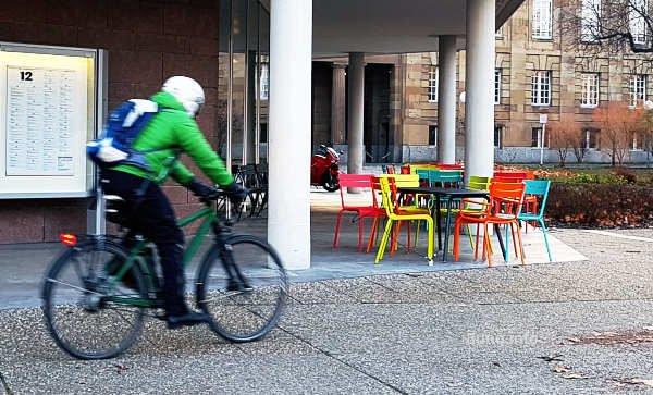Radfahrer mit grüner Jacke fährt an bunten Stühlen vorbei