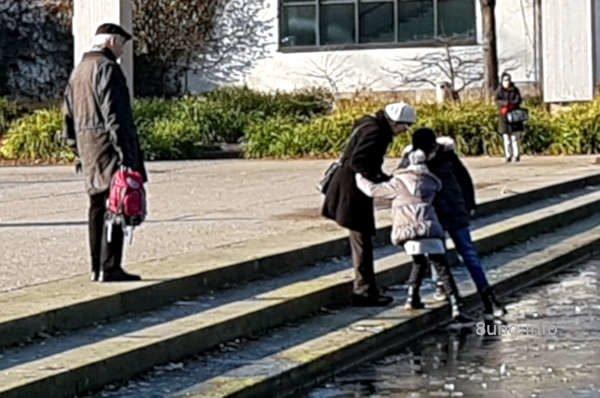 Kinder probieren, ob das Eis auf dem Wasser sie trägt